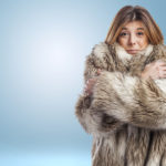 portrait of a pretty young woman wearing a fur coat